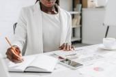 oříznutý pohled afrických amerických dospělých podnikatelka v bílém formální oblečení psaní v poznámkovém bloku nebo při práci v kanceláři