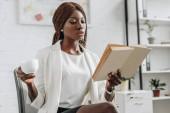 vážné afrických amerických dospělých podnikatelka v bílém formální oblečení, čtení knih a hospodářství šálek kávy v moderní kanceláři