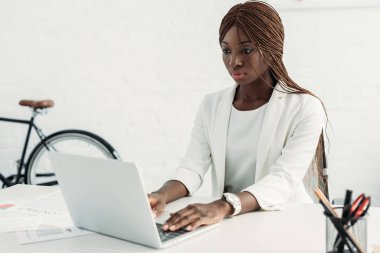 serious african american adult businesswoman sitting at computer desk and working in office