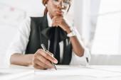 Selektivní fokus afroamerické ženy dospělých architekta v brýlích pomocí pera a práci na dokumentech v úřadu