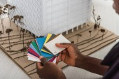 cropped view of african american adult female architect holding color palettes and working on construction project