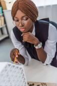 portrét afroamerické ženy dospělých architekta v brýlích podržením pera a pracuje na projektu výstavby v úřadu