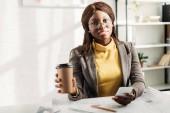 africké americké ženské architekt v brýlích drží kávu jít, pomocí smartphone a práci u stolu na projektu s plány