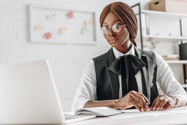 Attractive african american adult businesswoman in glasses sitting at computer desk and working in office stock vector