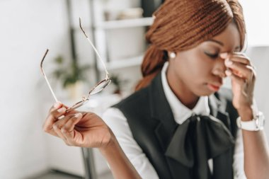 sick african american adult businesswoman touching her forehead and feeling unwell at workplace