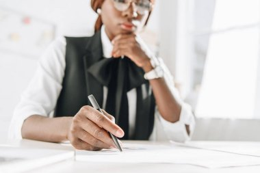 Selective focus of african american female adult architect in glasses using pen and working on documents in office stock vector