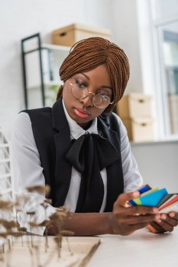 serious african american female adult architect in glasses holding color swatches and working on construction project in office