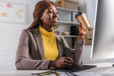 Smiling adult african american adult businesswoman sitting at computer desk, drinking coffee and using graphic tablet stock vector