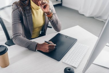 partial view of african american designer using graphic tablet at desk in modern office