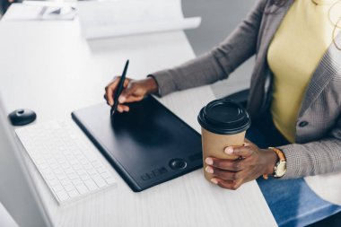 partial view of african american designer holding coffee to go and using graphic tablet at workplace