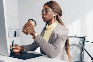 serious african american adult businesswoman sitting at computer desk, drinking coffee and using graphic tablet