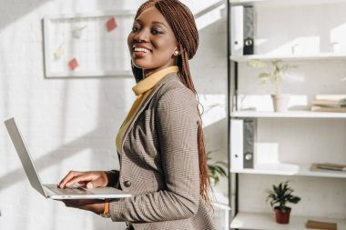 african american adult businesswoman holding laptop at workplace, smiling and looking at camera
