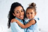 mosolygó afro-amerikai anya és lánya, átölelve a konyhában, és látszó-on fényképezőgép