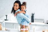 africká americká matka dává piggyback dcera v kuchyni, domácí koláčky na stole