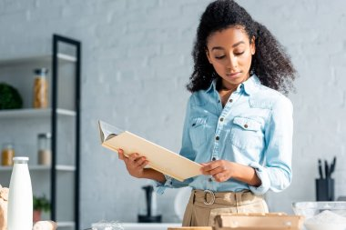 attractive african american girl holding cookbook in kitchen