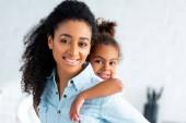 Veselá africká americká matka dává piggyback roztomilou dcerku v kuchyni