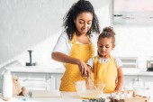 Fotografie African american Mutter und Tochter Teig vorbereiten und schlagen Eier in der Küche