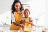 afro-amerikai lánya és anyja előkészítése és keveréshez tésztát, konyhában, kamera nézett mosolyogva