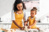 african american mother and daughter kneading dough together in kitchen