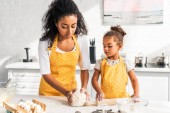 african american mother and daughter kneading dough together on table in kitchen