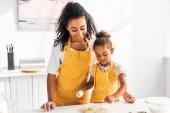 africká americká matka a dcera kolejových těsto s váleček v kuchyni