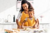 africká americká matka pomáhá dcera kolejových těsto s váleček v kuchyni