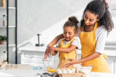 African american mother and daughter in yellow aprons whisking eggs for dough in kitchen stock vector