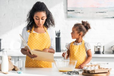 African american mother reading cookbook and daughter whisking eggs for dough in kitchen stock vector