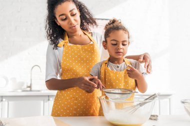 African american mother and daughter preparing dough and sieving flour together in kitchen stock vector