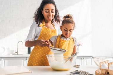 African american mother helping daughter preparing dough and sieving flour in kitchen stock vector