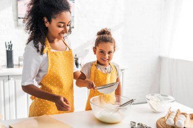 Happy african american mother and daughter preparing dough and sieving flour together in kitchen stock vector