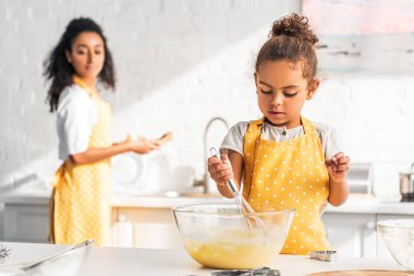 selective focus of african american daughter preparing and whisking dough in kitchen