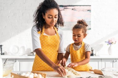 African american mother and daughter kneading dough in kitchen stock vector