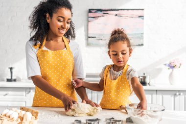 Smiling african american mother and daughter kneading dough for dessert in kitchen stock vector