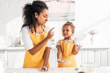 grimacing african american mother and daughter preparing dough and having fun with flour in kitchen