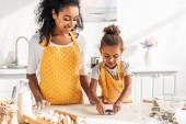 african american mother and daughter preparing cookies with molds in kitchen