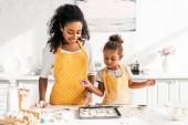 africká americká matka a dcera na zásobník v kuchyni při pohledu na soubory cookie