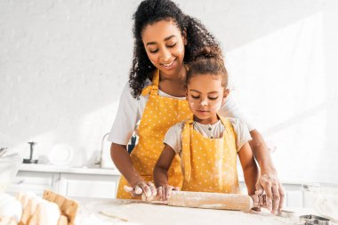 smiling african american mother helping daughter rolling dough with rolling pin in kitchen