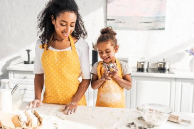 happy african american mother and daughter looking at dough for cookies in kitchen