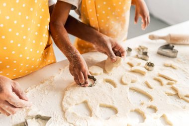 cropped image of african american mother and daughter preparing cookies with molds in kitchen