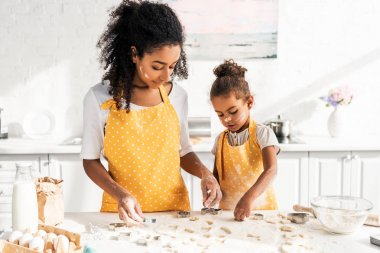 African american mother and daughter in yellow aprons preparing cookies with molds in kitchen stock vector