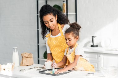 African american mother and daughter applying oil on unbaked cookies together in kitchen stock vector