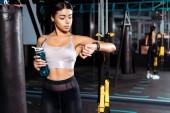 Fantastický sportovní dívka drží láhev s vodou při pohledu na fitness tracker v tělocvičně sportovní