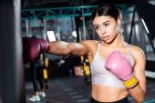 Atraktivní boxer dívka v Boxerské rukavice házení údery v tělocvičně