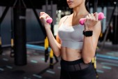 Fotografie Cropped view of strong female doing dumbbells exercises in fitness gym