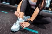 Částečný pohled sportovní dívka vázání tkaničky v posilovna