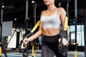 Oříznutý pohled atraktivní sportovní dívka cvičení s popruhy suspenze v tělocvičně sportovní