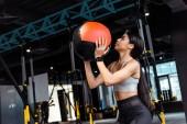 Attraente ragazza sportiva allenamento con palla medica in palestra fitness