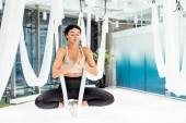 Relaxed Girl practicing antigravity yoga in lotus position with namaste mudra gesture in studio