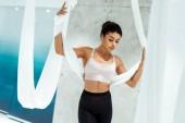 Atraktivní sportovní dívka cvičí jógu v houpací síti ve studiu